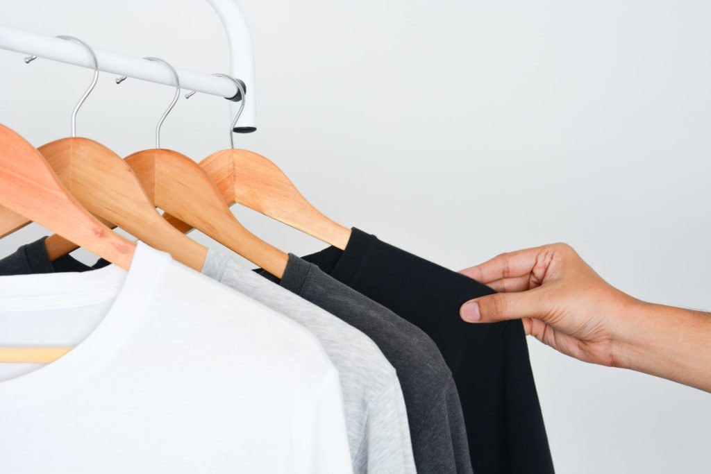 man's hand choosing black color t-shirt from collection of black, gray and white color t-shirt hanging on wooden clothes hanger in closet or clothing rack over white background